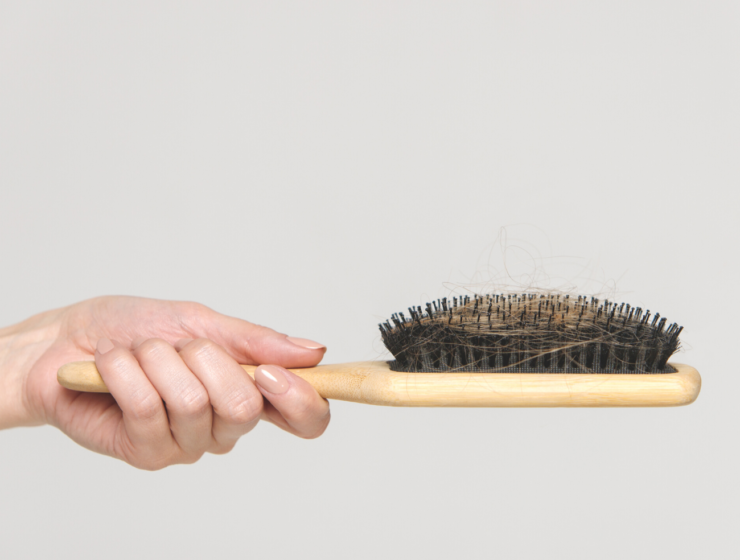 postpartum mom holding a hormone hair loss on a brush