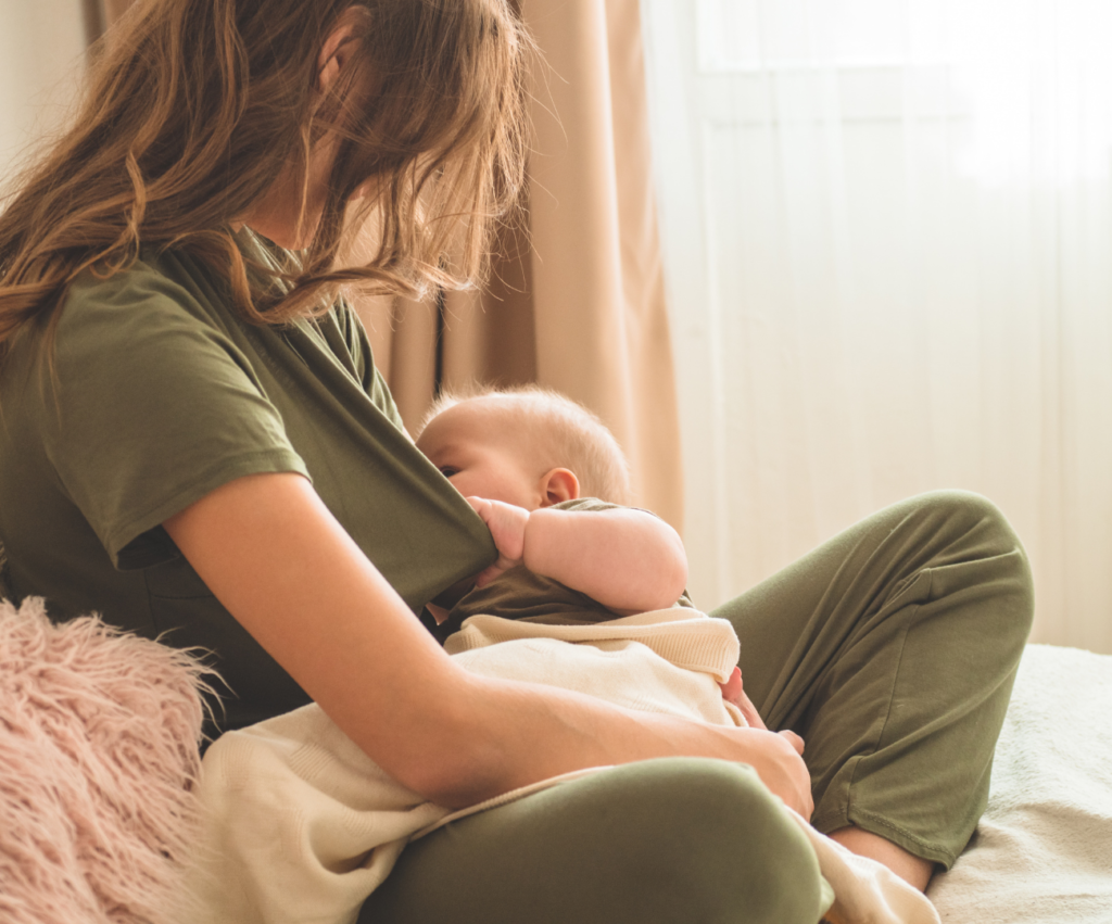 new mom sitting on bed breastfeeding baby