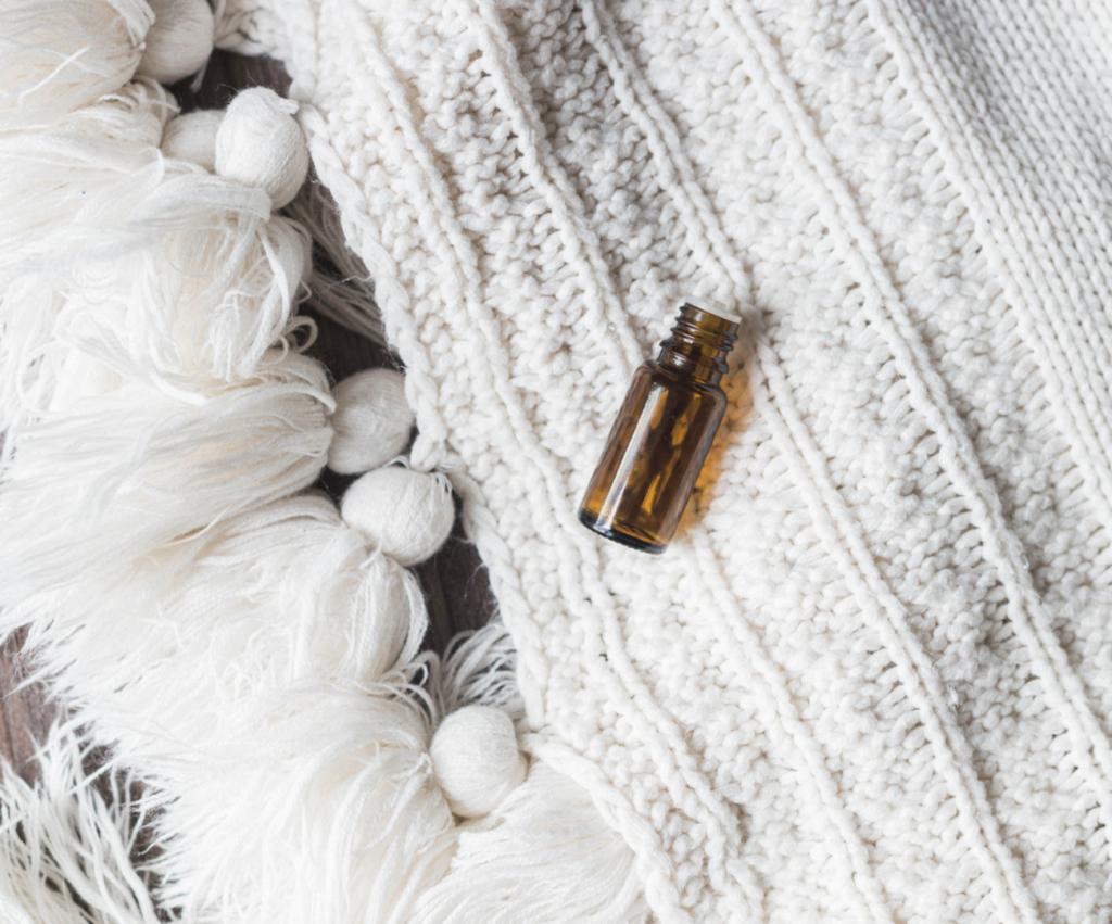 essential oil bottle on a cream knit blanket