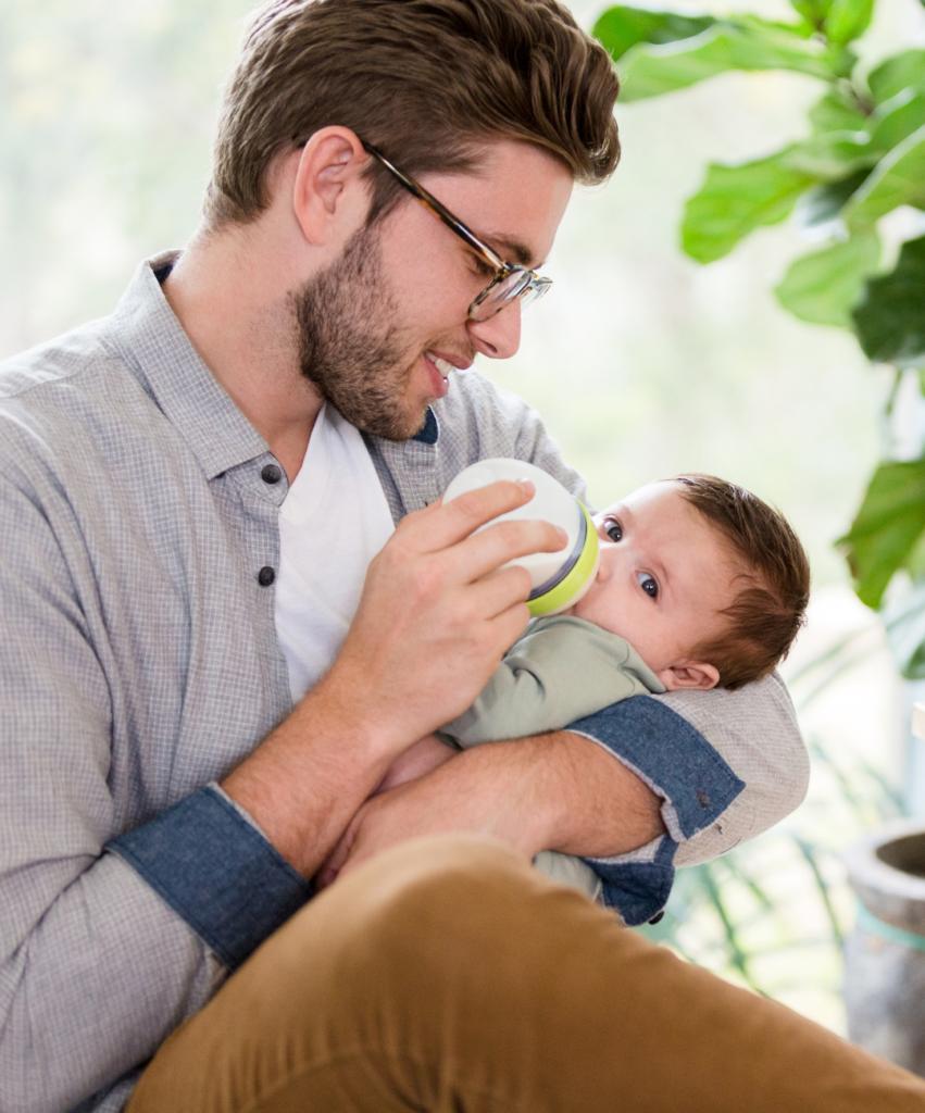 dad bottle feeding baby in lap