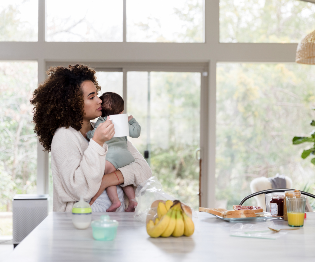 new mother holding her baby and coffee mug looking tired