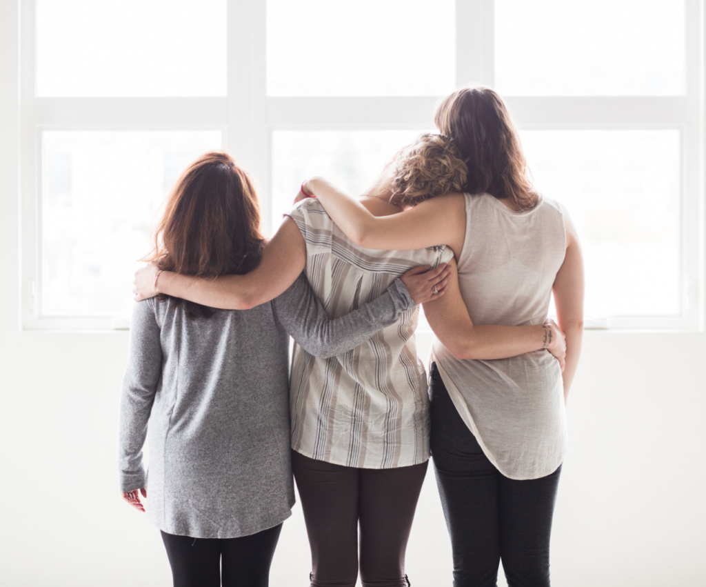 three woman with their arms over each others shoulders