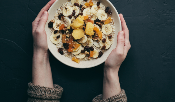 woman with bowl of oatmeal topped with fruit