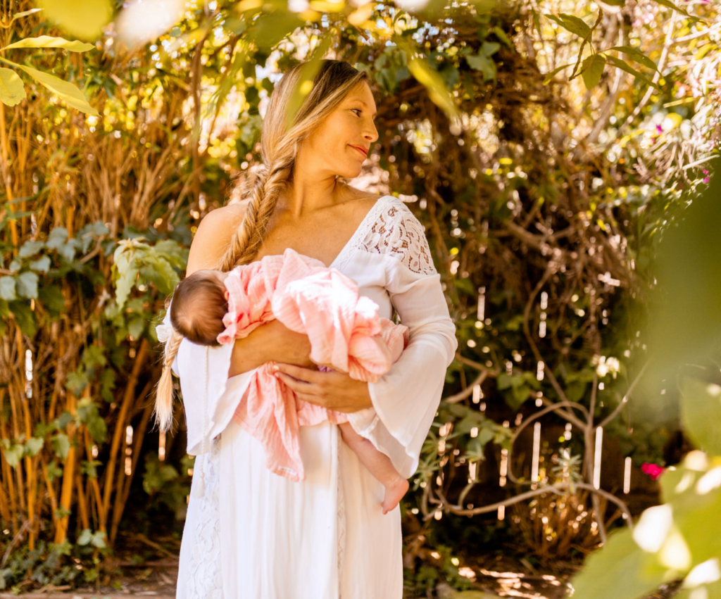 new mother holding newborn baby in a white gown