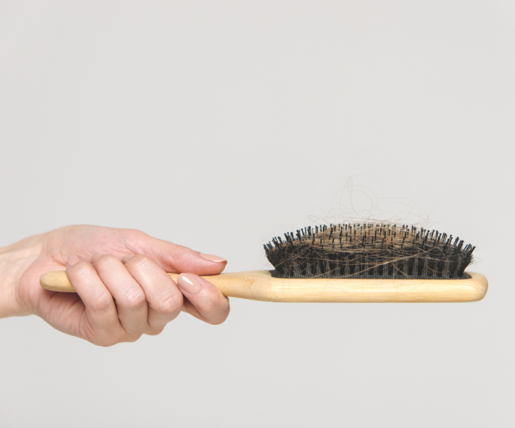woman holding a hairbrush with hair