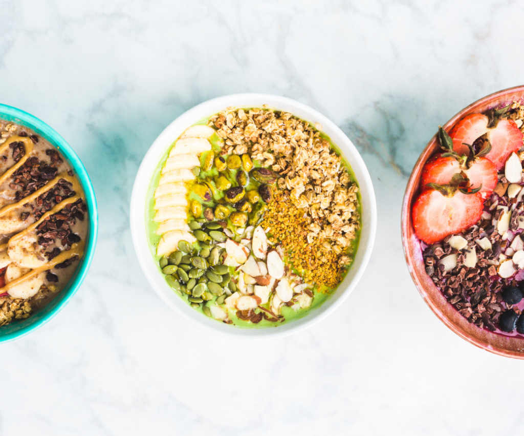 three smoothie bowls with a variety of toppings