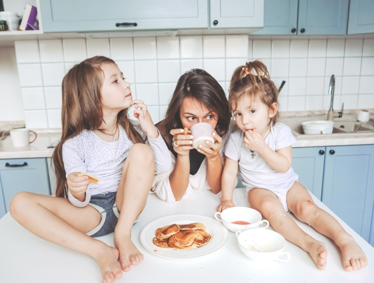 mom drinking coffee at the counter with her daughters