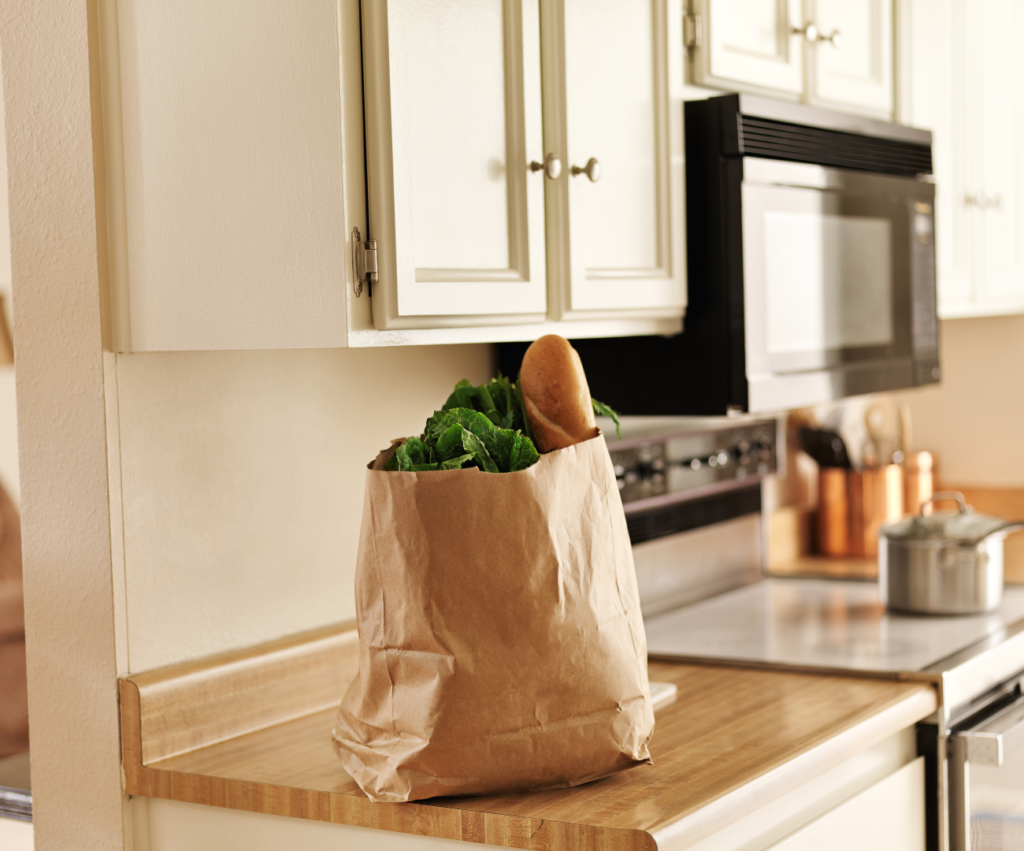 paper grocery bag on kitchen counter with bread and kale