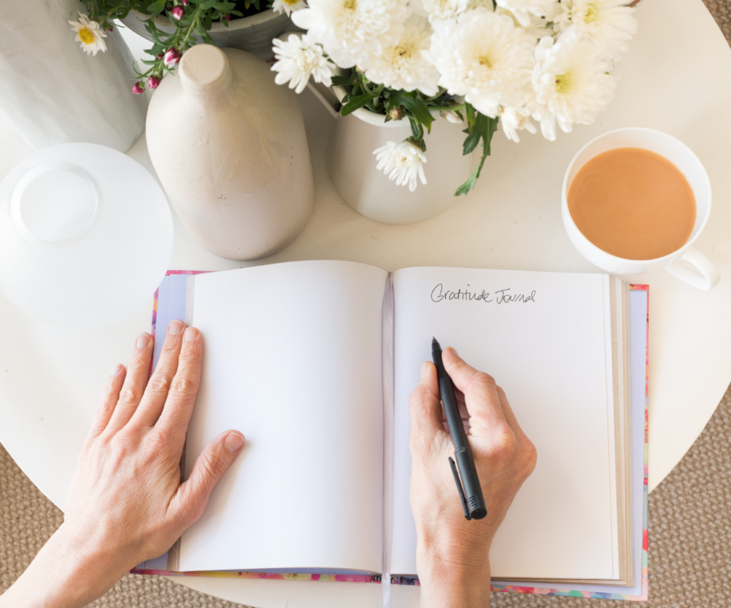mom writing in a journal with a cup of coffee and flowers