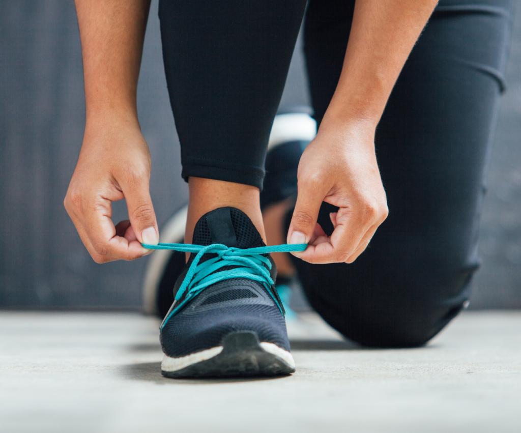 woman tying her shoes to run