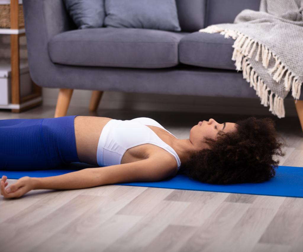 woman laying down on a yoga mat meditating