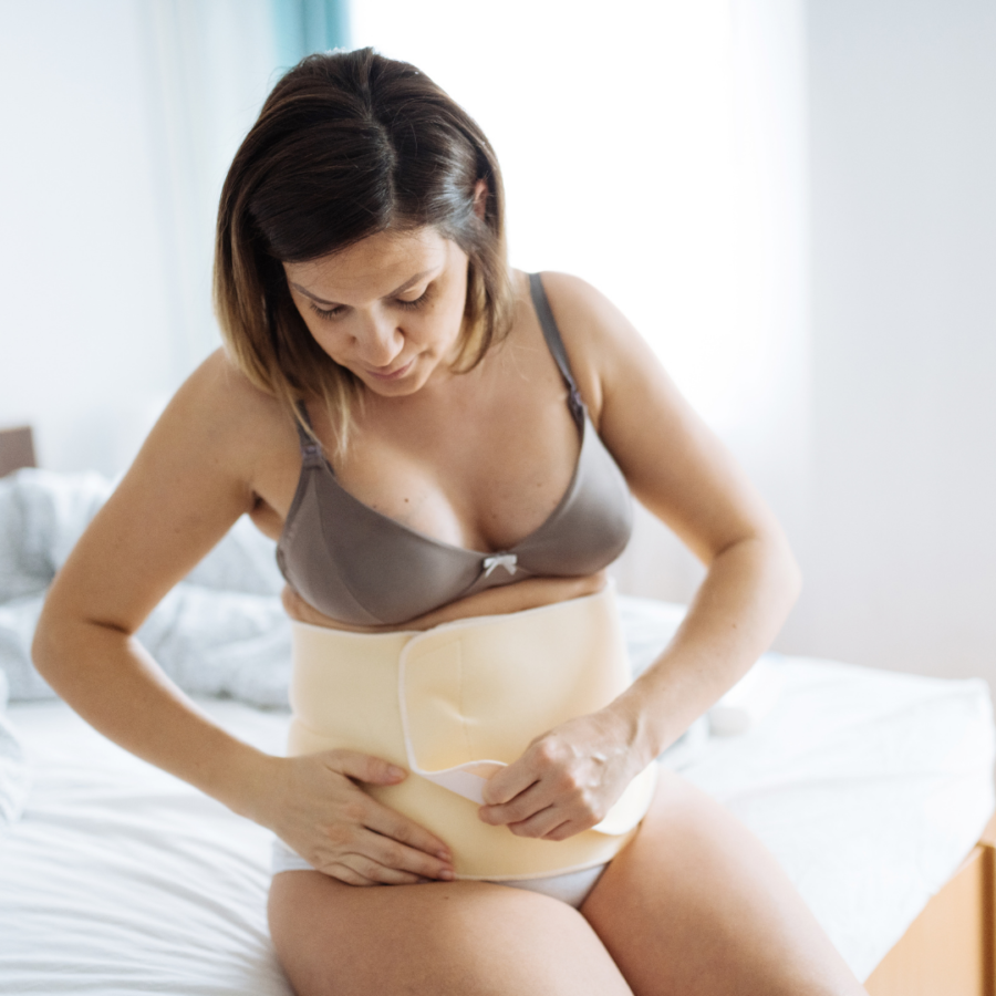 woman wrapping herself with postpartum band