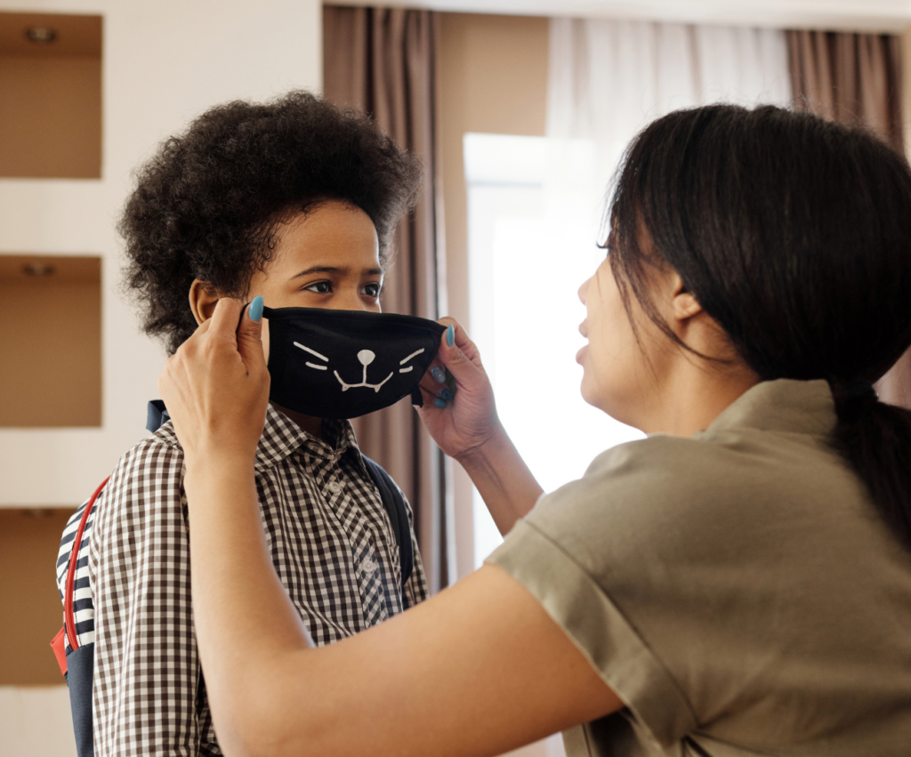 mom putting a mask on her son