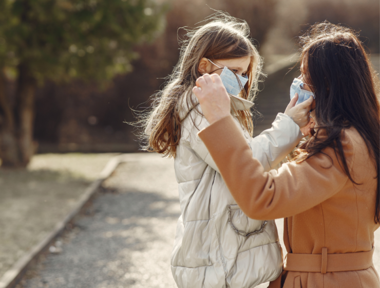 mom putting a mask on her daughter