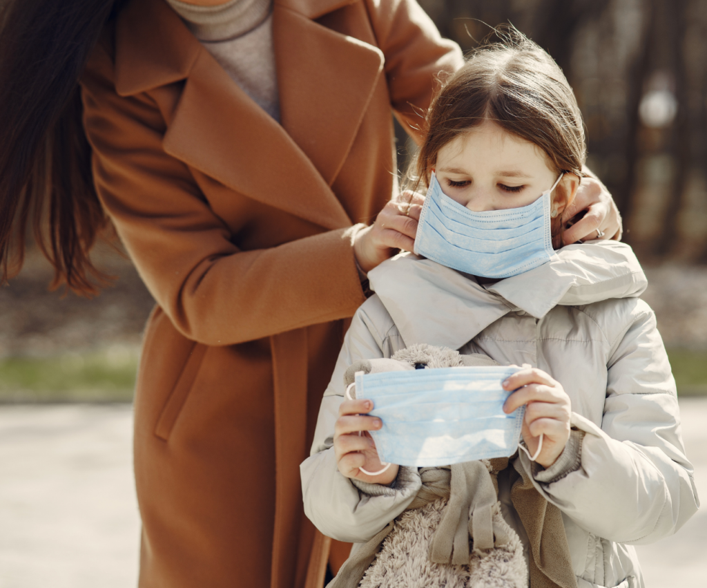 mom putting a paper mask on her daughter