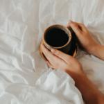 woman holding mug of tea on bed