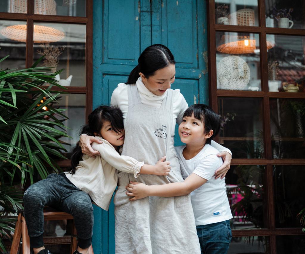 mom hugging her two kids