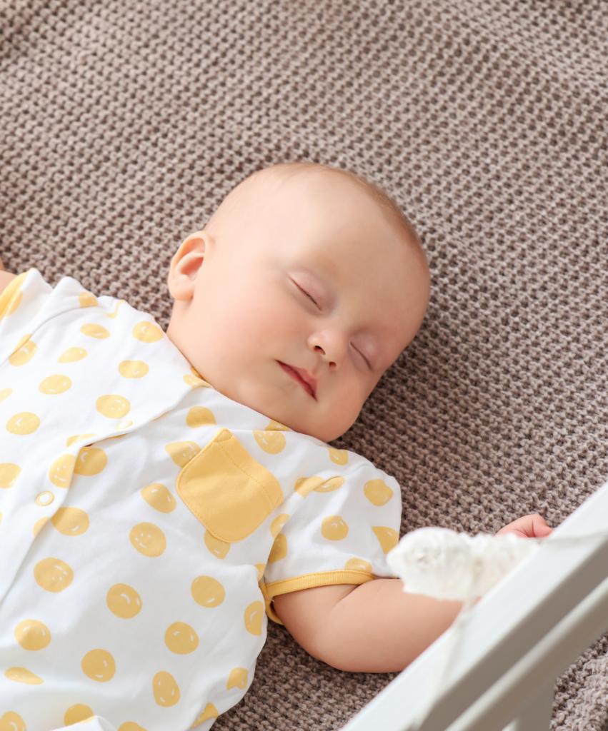 baby sleeping in crib in a yellow sleeper