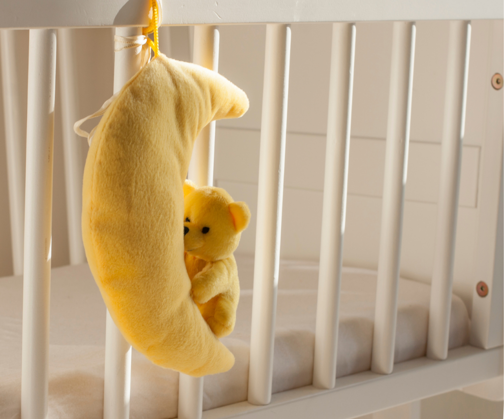 baby crib with hanging stuffed animal