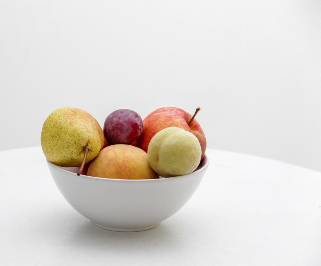 bowl of various fruit on white countertop