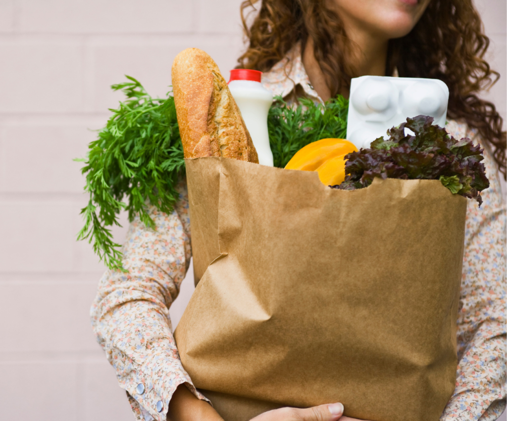 person holding a grocery bag with food
