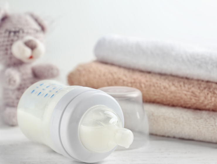 baby bottle with formula and small blankets nearby